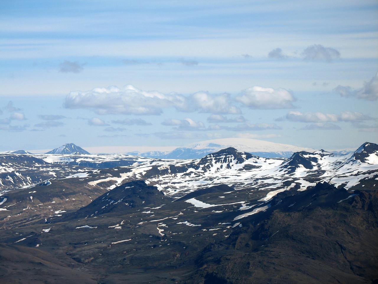 Bak við ýmis (mér) óþekkt fjöll suðaustan Hítardals sjást Baula og Eiríksjökull.