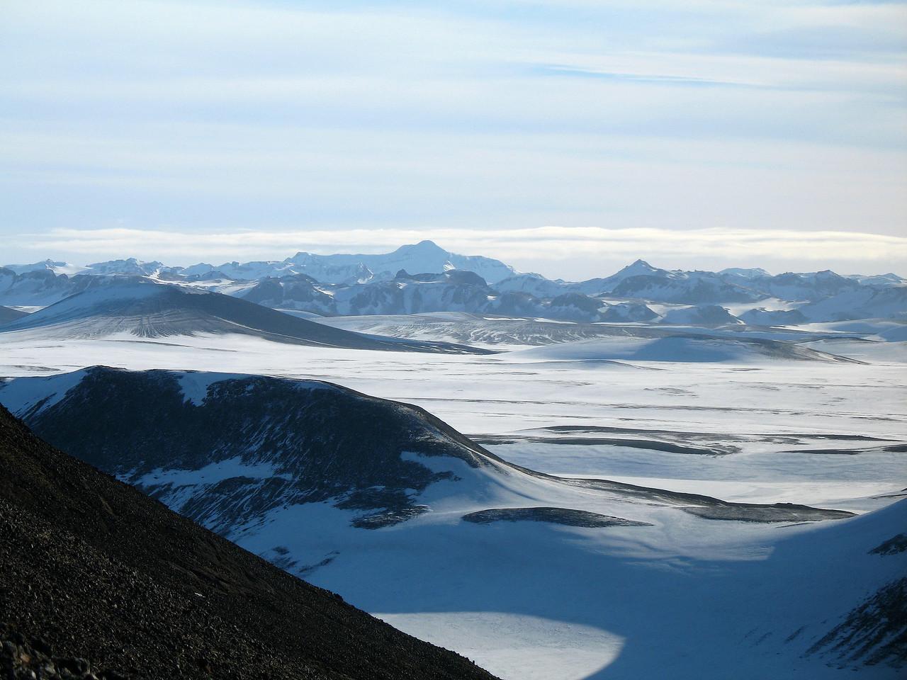 Útsýni til austurs, Sveinstindur gnæfir hæst, hægra megin við hann ber Gretti við himin, Ljónstindur nær er lægri.