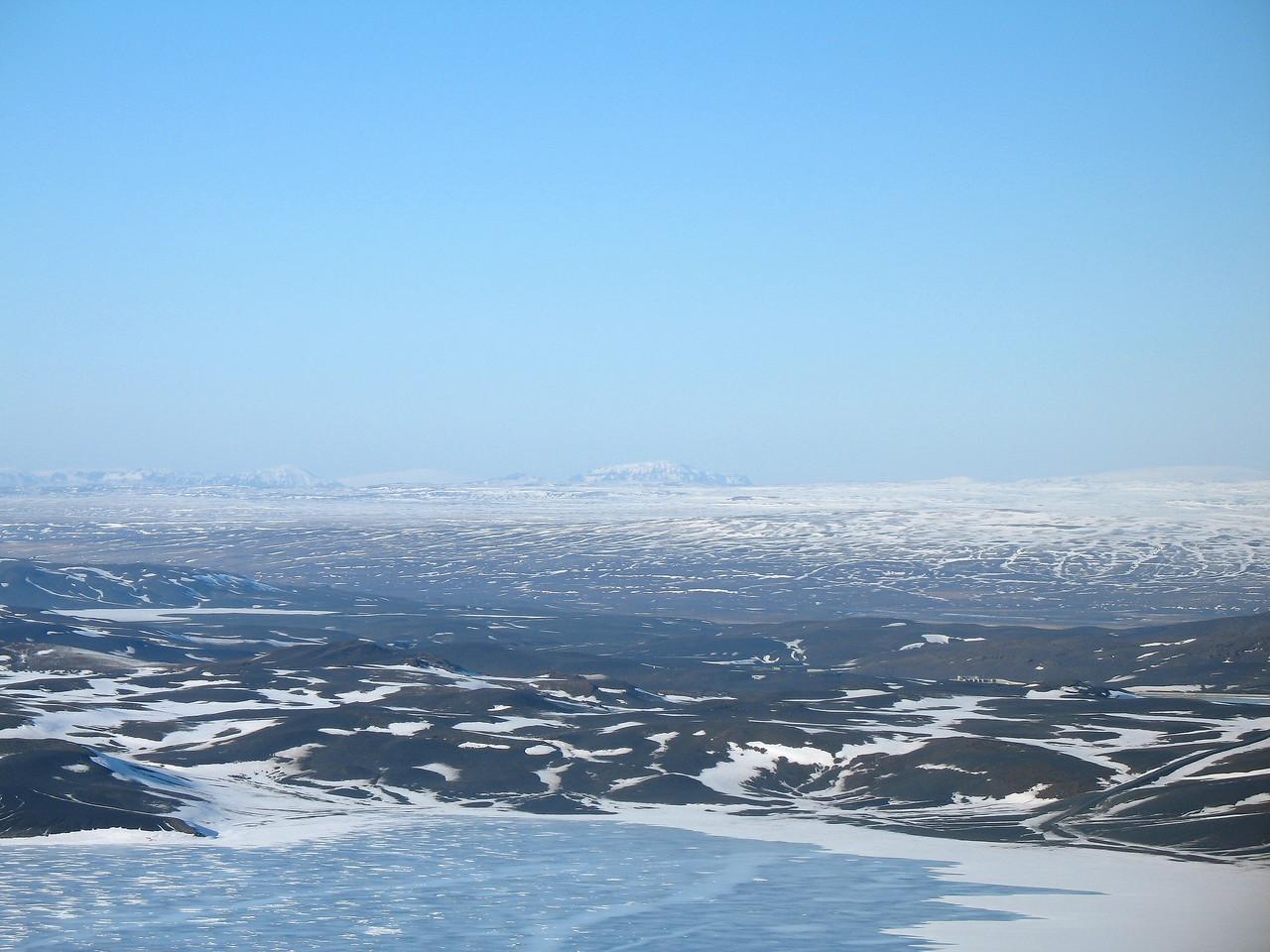 Útsýnið af toppnum - í vestri má óljóst greina Skriðu, Rauðafell, Högnhöfða, toppinn á Skjaldbreið og Kálfstind. Hlöðufell gnæfir á miðri mynd, síðan grillir í toppinn á Stóra-Björnsfelli og að lokum jökulhvel Þórisjökuls.