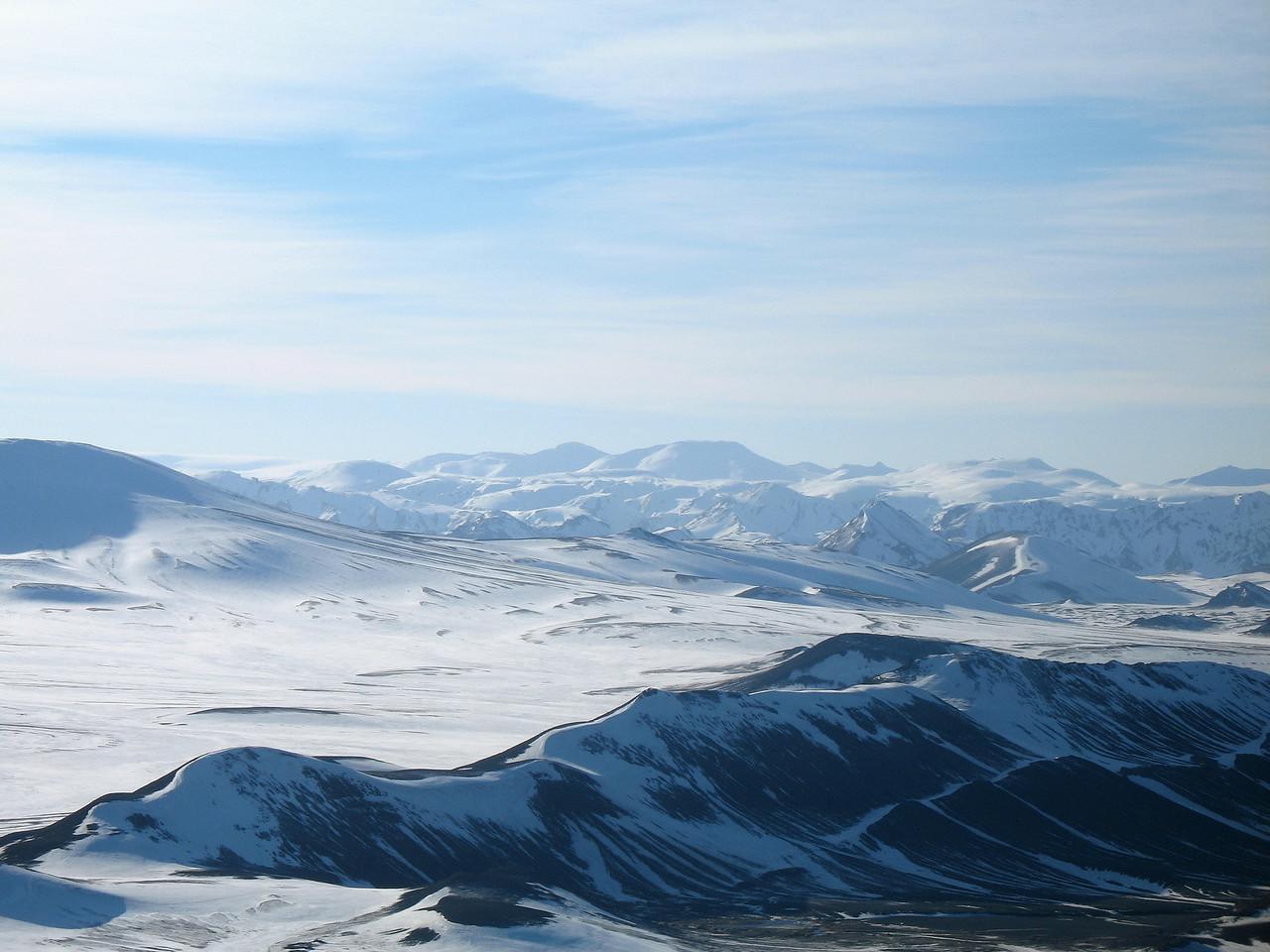 Útsýnið af toppnum - Háskerðingur fyrir miðri mynd með Skerínef til vinstri við sig, lengst til hægri sést Söðul bera við himin. Neðan Söðuls (nær) sjást Suðurnámur, Norðurnámur við austurenda þeirra.