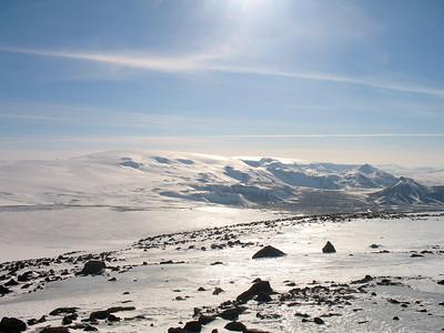 Hér er horft yfir farinn veg. Ef vel er að gáð sést í toppinn á Hlöðufelli (dökkur díll) gægjast yfir öxlina milli Langjökuls og Geitlandsjökuls. Hérna megin við Þórisjökul sést Prestahnjúkur á milli Geitlandsjökuls og Hádegishnjúks.