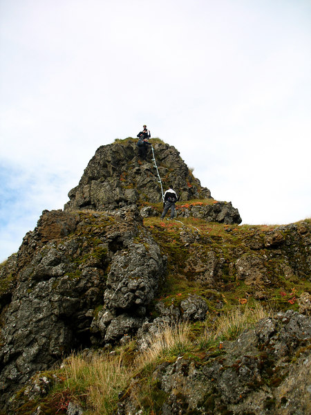 Skarphéðinn situr á Arnarþúfu og lóðsar fólk niður, Þóroddur stendur neðan efsta kaðals.