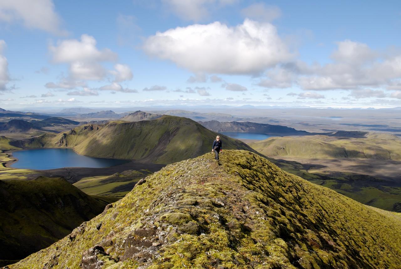12:54 Gerður að komast á tindinn, í baksýn Herbjarnarfellsvatn og Hrafnabjargavatn.