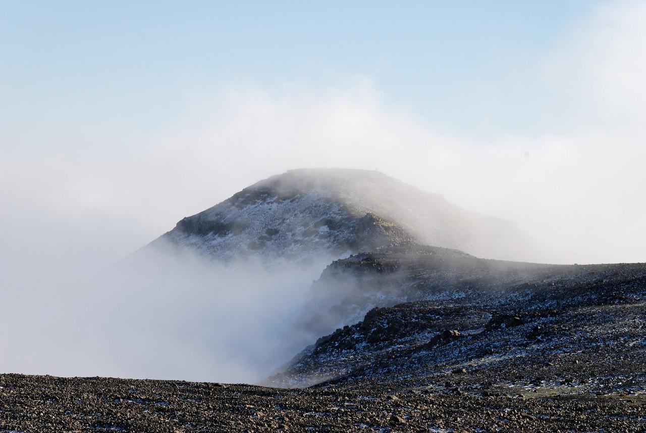 14:46 Litið til baka, Hátindur sveipaður þokumóðu og hrímgrár þar sem sólin nær ekki til.
