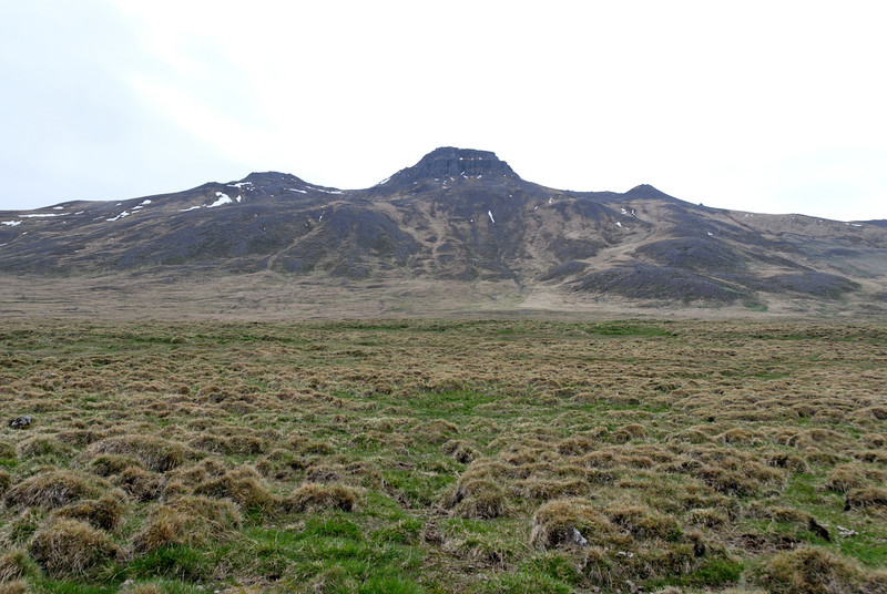 17:01 Spákonufell séð frá þjóðveginum. Leið okkar lá í um söðulinn (Bókin kallar þetta skarð) vinstra megin við klettaborgina, svo hægri beygja og upp.