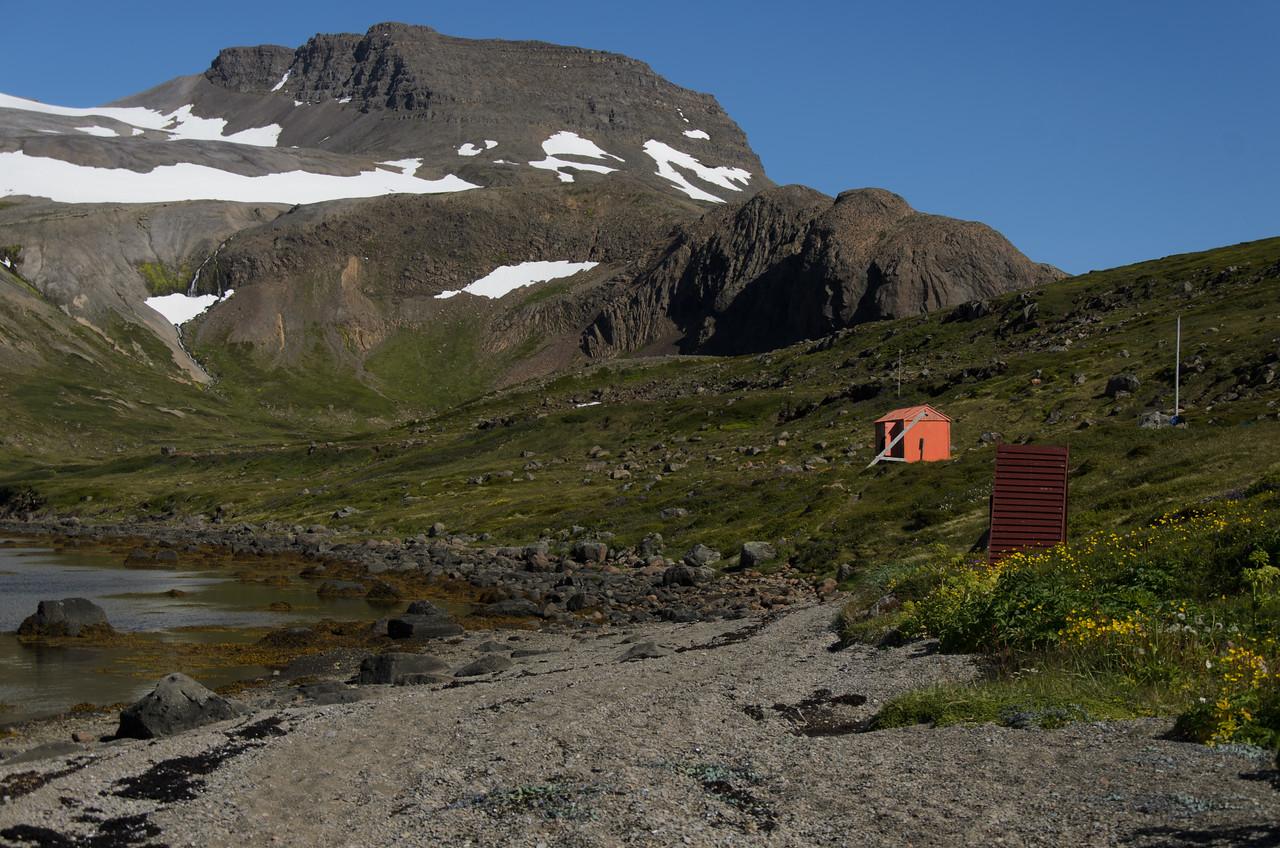 Hærra-Hattarfjall gnæfir yfir Gýgjarsporshamri í botni Hrafnfjarðar. Nær sést neyðarskýli.