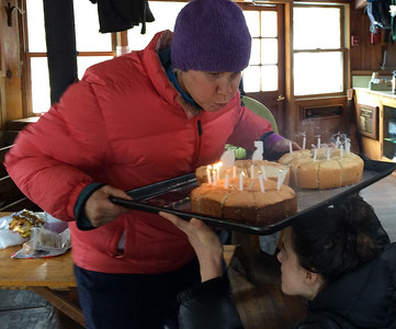 Jen Botzojorns blows out the candles at her  50th birthday party -  Lonesome Lake hut in Franconia Notch, NH.