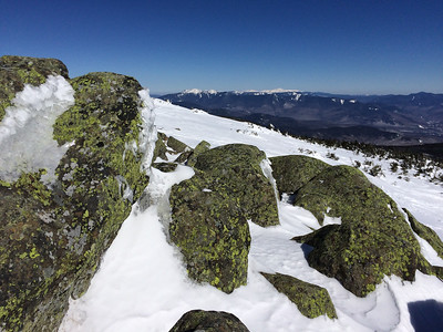 The summit of Moosilauke on a beautiful day with the Franconia and Presidential Range in the background.
