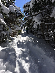 The ridgeline between north and south peak is a busy place with many skiers and a heavy cover of snow.