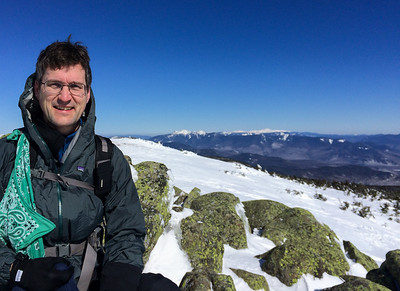 David on the summit of Moosilauke with the Franconia and Presidential Range in the background.