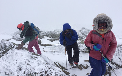 Jen, Lelia, and Andy reach the summit of Mount Moosilauke in a fierce wind and snowstorm.