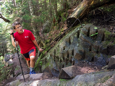 Andy scrambles up the Beaver Brook trail, Mount Moosilauke. Many parts of the trail involve bedrock removed by drilling, with handholds and footsteps drilled into the rock.