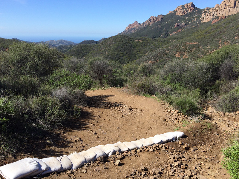 A view toward the Pacific ocean with the Sandstone peak 'backbone' at right. The trail was badly eroded due to heavy use and poor design; the park laid out ad hoc waterbars using sandbags.