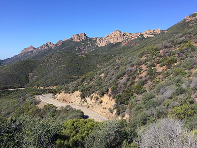 A bicyclist cranks up the winding road, with the 'backbone' section of my hike behind him.