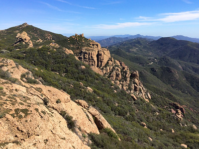 Sandstone Peak in sight - the high point of the hike ahead - with a group of hikers on the bump in middle ground.