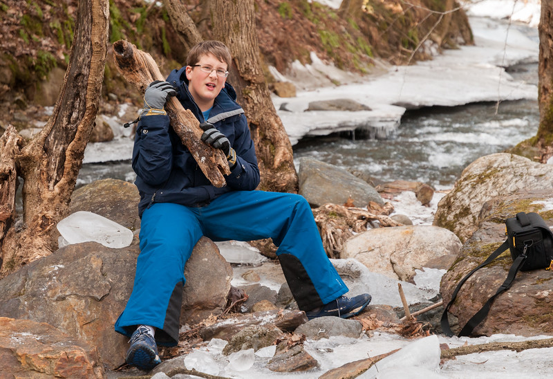 Andy plays with ice, sticks, and rocks near the frozen Hewes Brook.