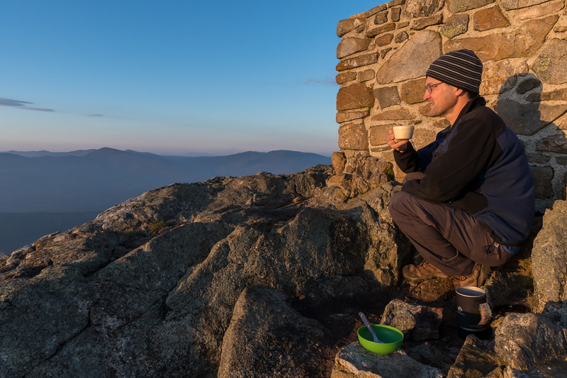 David enjoying breakfast and the sunrise from Avery Peak, Bigelow Mountain, Maine.