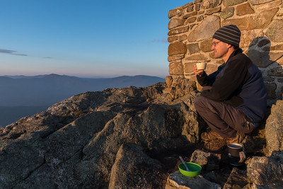 David enjoying breakfast and the sunrise from Avery Peak, Bigelow Mountain, Maine.