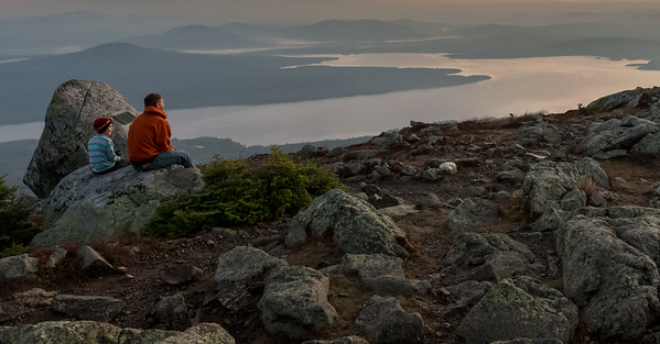A father and son enjoy the sunrise from Avery Peak, Bigelow Mountain, Maine.