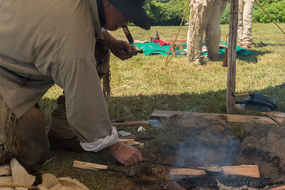 A re-enactor shows us they used to make lead shot using molten lead and a ball mold.