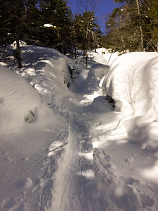 The herd path crosses Panther Brook, on the steep slope of Panther mountain.  Deep snow creates steep banks.
