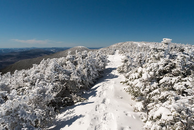 Deep snow on Moosilauke Ridge, with South Peak on the background, provide hikers steady views over the krumholz.