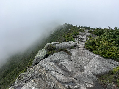 Approaching the clouded summit, the trail follows a rocky ridgeline.