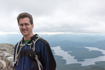 David celebrates his 46th peak near the summit of Whiteface, with a view of Lake Placid at rear.