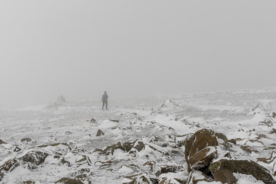 Lelia approaches the Moosilauke summit on a windy and cloudy winter day.
