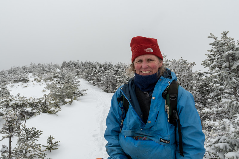 Lelia pauses on the Moosilauke ridgeline, preparing to summit on this cloudy winter day.