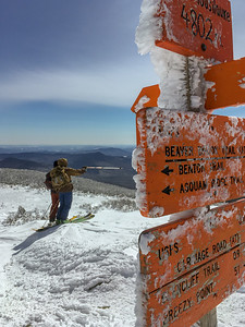 Two hikers examine the view on the summit of Moosilauke, with the summit signs in the foreground.