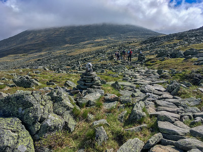 A group approaches Mount Washington in the clouds.