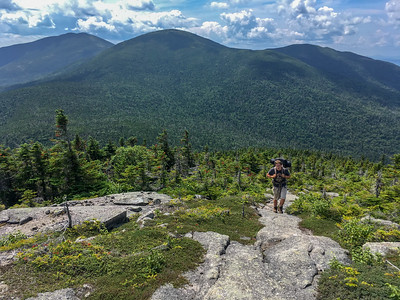 Andy climbs Saddleback Junior, with The Horn and Saddleback Mountain behind, on the A.T. in Maine.
