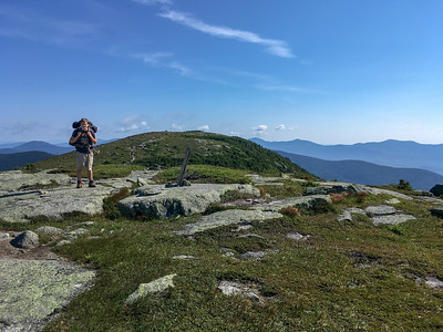Andy turns to face me as we approach the summit of Saddleback Mountain, in background, on the A.T. in Maine.