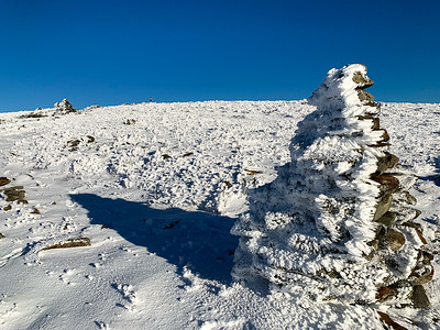 The summit sign beckons in the distance while rock cairns hold rime-ice feathers.