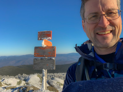 David on the summit of Moosilauke on a blue-sky day with moderate temps and low wind.
