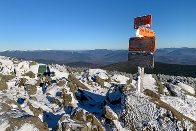 The summit sign on Moosilauke, with distant views of Franconia and Presidential Ranges beyond.
