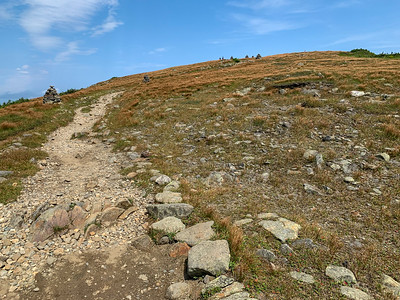 Approaching the summit via the Carriage Road; two hikers and several cairns in the distance.