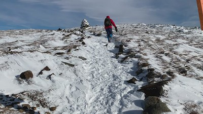 Kathy battles strong winds as we approach the summit of Moosilauke.