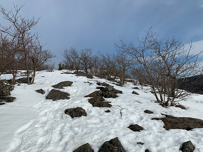 The snow is thin on the windswept ledges of Mount Roberts.
