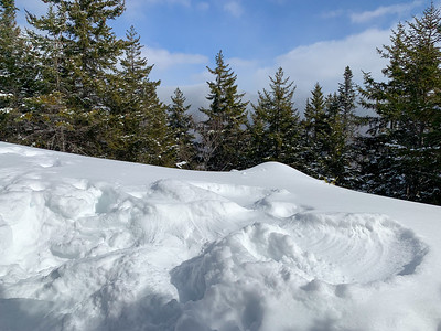 A snow angel on Mt. Pemigewasset, with the peaks of Franconia Ridge peeking out from the clouds and trees.