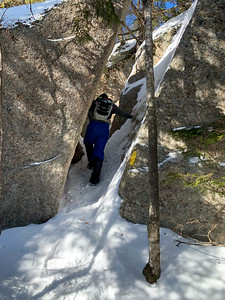 Andy follows the trail up Mount Welch as it squeezes between a split granite boulder.