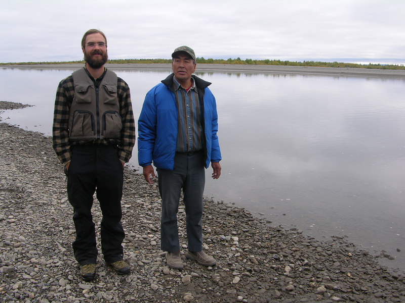 Meet Ricky Ashby, the nicest guy in Northwest Alaska . . . but first, how we got to this picture . . . Much has happened since we broke camp on Day 16 (August 27).  We spent the first half of Day 16 floating twenty miles to Noatak Village.  On the 435 miles of the Noatak River there is only this one native village, which is at river mile 372, with a population of about the same, something like 350.  The village is on the west side of the river but abundant braids make it easy for floaters to miss the village altogether.  Moreover, during the last two years the river had shifted course enough to make the village inaccessible from up river.  This is not a problem for the powerboat guys, but we did have some trouble making it back up river after necessarily floating half a mile past the village.  As we rowed and lined up the moderately flowing channel towards the village, a man eagerly watched our approach from the bluffs above and offered various words of encouragement and advice.  After we reached the village the onlooker, Ricky Ashby, welcomed us and almost immediately invited us into his home for dinner.  We placed our meat in his shed and went into his home.  Ricky prepared coffee while Ian brought in some of our fresh caribou meat from the shed.  We were both somewhat in a daze (it had been awhile since we had sat at a table, talked to anyone besides each other, had been in a heated home, etc.) as Ricky talked to us while he prepared a meal.   Ricky magically cut meat, prepared rice, and made gravy while we basked in the glow of the warmth of his home and conversation.<br /> <br /> This photo of Ricky Ashby with Ian was taken on the morning of Day 17 (August 28).  That morning we contacted Bering Air and arranged for our caribou meat to be flown to Kotzebue and frozen.  We deemed this expedited freezing of the meat necessary because the mid-day temperatures were significantly higher than the ideal 40's range, and while the final stretch of the river between Noatak Village and Kotzebue was only ~60 miles, reportedly slow currents and wind would likely hamper (or halt for days) our heretofore speedy progress.  With these unknown factors in mind we chose not to risk meat spoilage during the next few days that it would take us to float to Kotzebue.  In fact, most river floaters go ahead and fly themselves back to Kotzebue from the Noatak Village airfield, but we obstinately opted to finish the river despite potential winds and a very slow current.