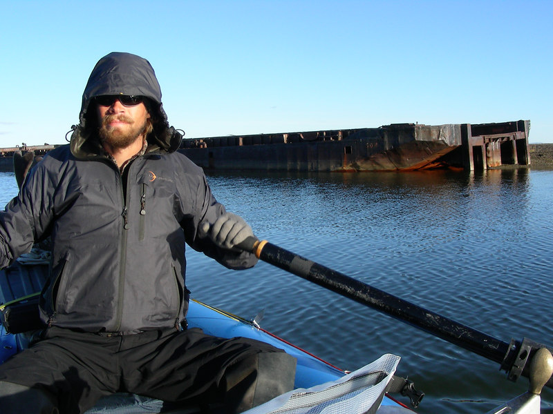 Trystan rows past a barge beached at the end of the Kotzebue spit.