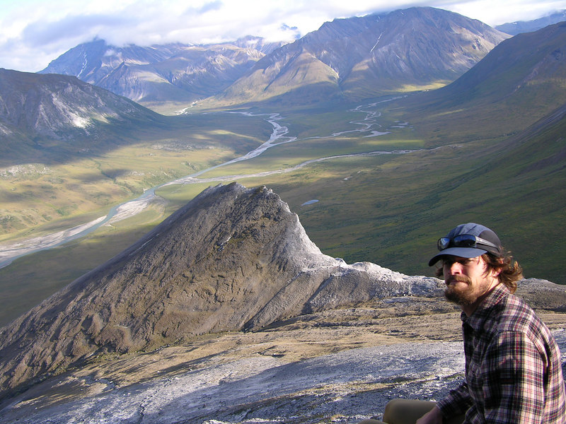 Trystan taking a look at the camera while considering the beauty of Igikpak (center of photo, shrouded in clouds).