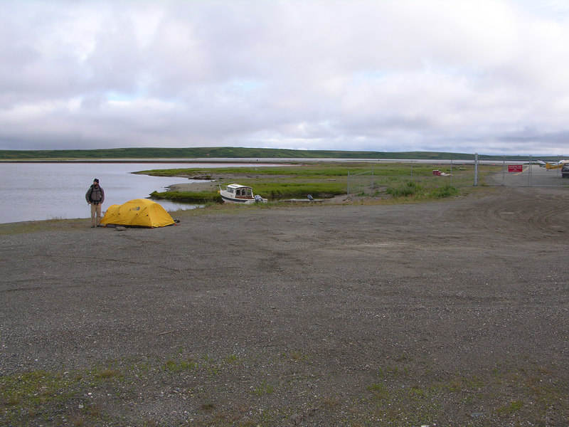 "Ian standing by our tent pitched on the edge of the Kotzebue lagoon .  This local ""campground"" lies at the end the airport behind Jim's (a local retired air taxi pilot) hanger."