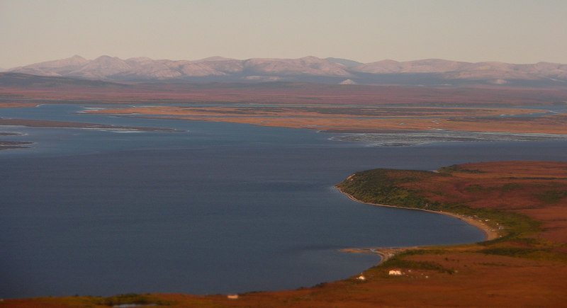 "This view shows our ""ocean"" crossing from the mouth (tan colored midground) to the bluffs north of Kotzebue (red and green point in the foreground). Only about 3 miles across, there is so much river input (the Noatak, the Kobuk, and the Selawik), that the water has only a hint of salt to it. Still, it's the Arctic Ocean, and we did, in fact, row across it!"