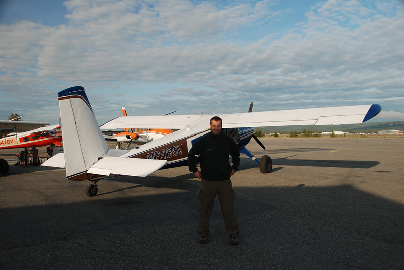 Devan, on the tarmac at the East Ramp of FAI, stands by our loaded Helio Courier that is ready to put us on the Charley River.