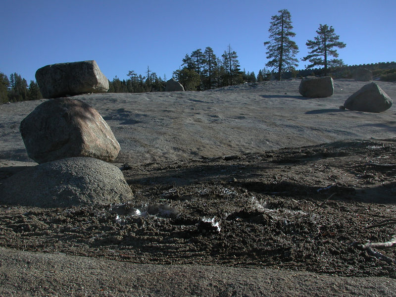 "View of glacially polished granite slab and glacial erratics (boulders).  The erractics were left in the receding wake of ice during the end of the last glacial maximum. (More recently, last night's ""needle-ice"" can be seen in center foreground)"