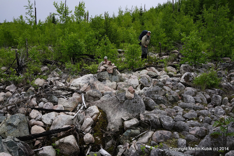 On the moraine.  Depending on sun light and clouds you may see these rock cairns, or, they may blend in the background.